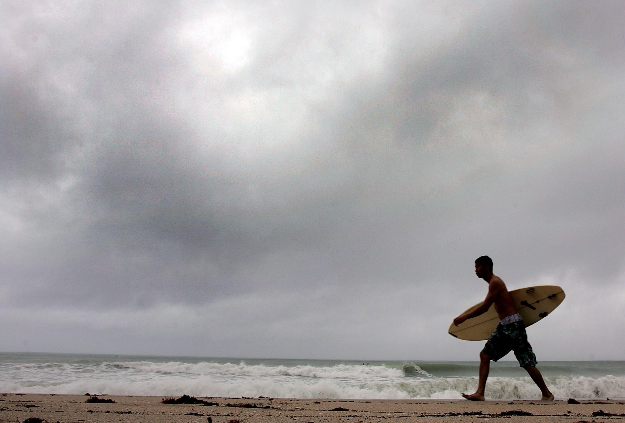 Surfer walking on beach in Fort Lauderdale, FL