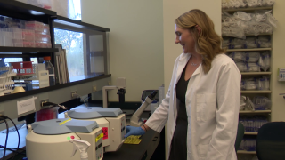 Tiffany Hensley-McBain demonstrates a centrifuge in a lab at the McLaughlin Research Institute