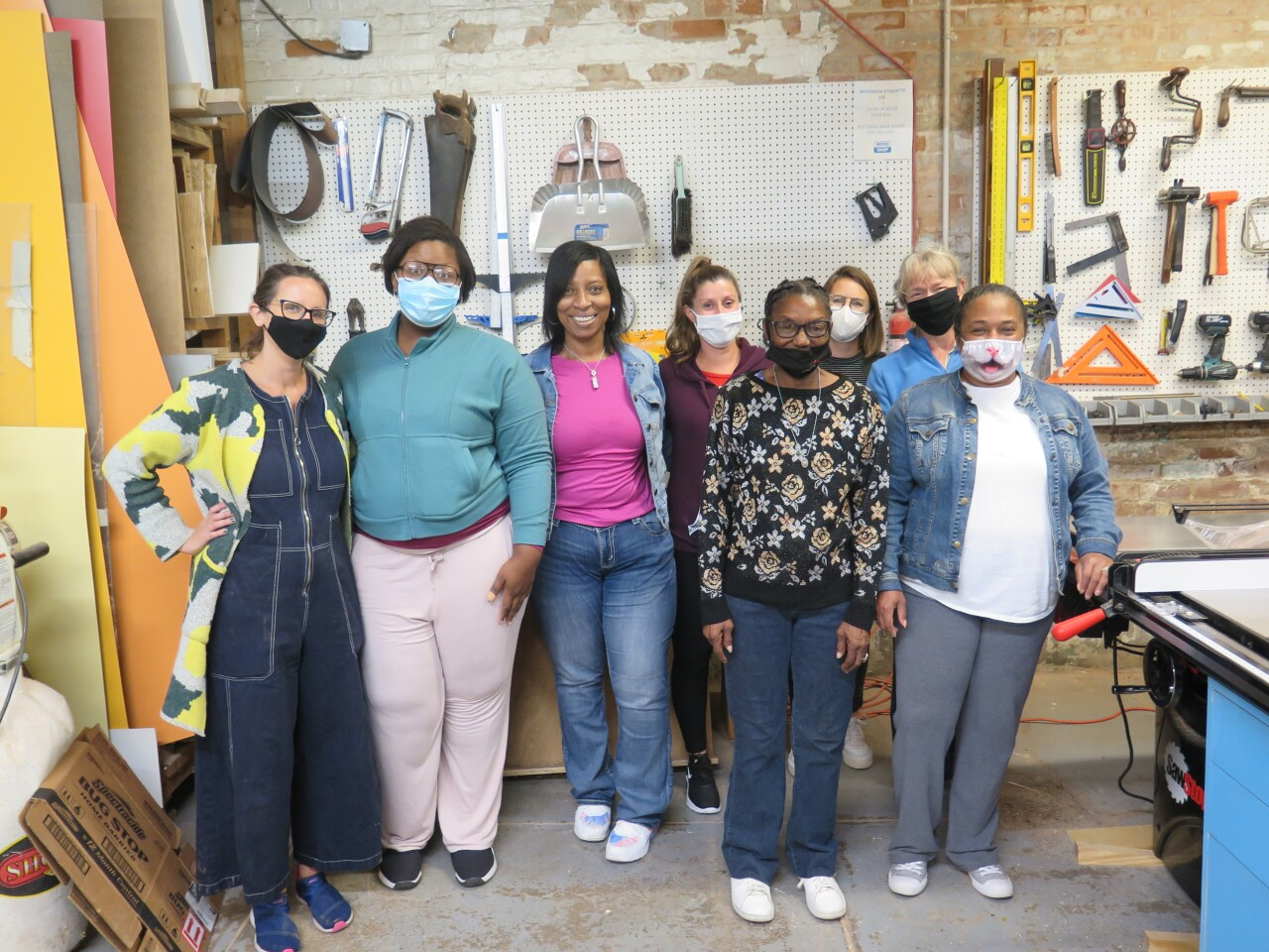 This photo shows eight women who are part of the Owning Your Own Voice woodworking class.