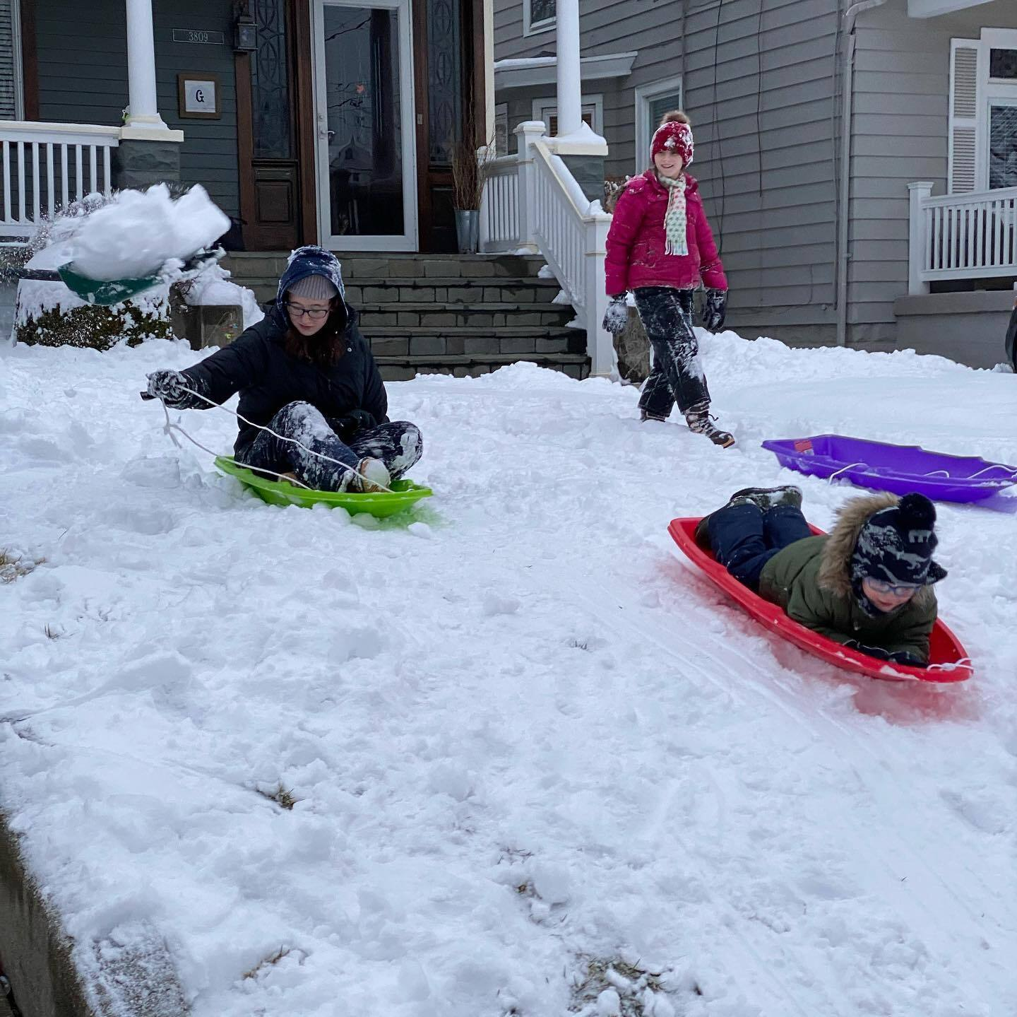 4-year-old Finley, 15-year-old Emma and 11-year-old Tessa enjoy a sled run in Norwood.