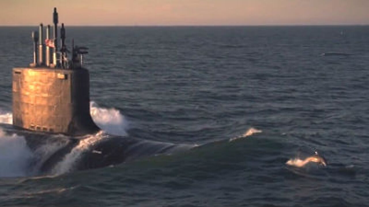 Dolphins surf new submarine's bow wave (video)