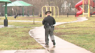 Corporal Ed Shinkle walks toward the Cincinnati park shelter registered as the home address of a convicted sex offender