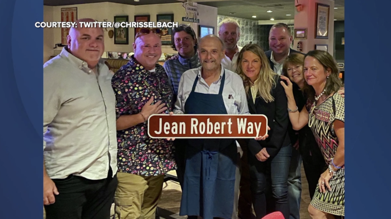 Friends and family celebrate an honorary street sign for chef Jean-Robert de Cavel.