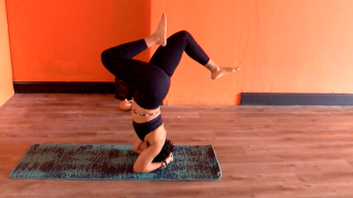 A woman balances upside-down on her elbows at InoarG Yoga, a Black-owned yoga studio in Madisonville.