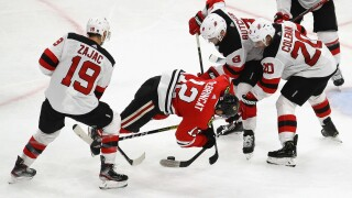 CHICAGO, ILLINOIS - DECEMBER 23: Alex DeBrincat #12 of the Chicago Blackhawks hits the ice battling for the puck with (L-R) Travis Zajac #19, Will Butcher #8 and Blake Coleman #20 of the New Jersey Devils at the United Center on December 23, 2019 in Chicago, Illinois. The Devils defeated the Blackhawks 7-1. (Photo by Jonathan Daniel/Getty Images)