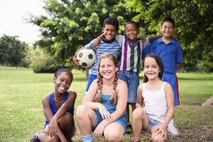 Multiethnic group of happy male friends with soccer ball