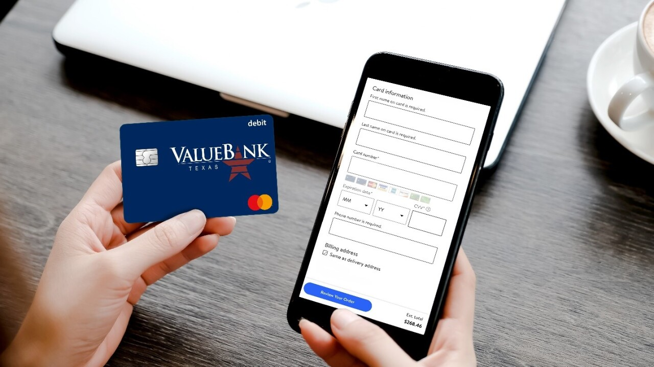 An image of a payment screen on a mobile smartphone being held by a customer holding a Value Bank debit card in their other hand.