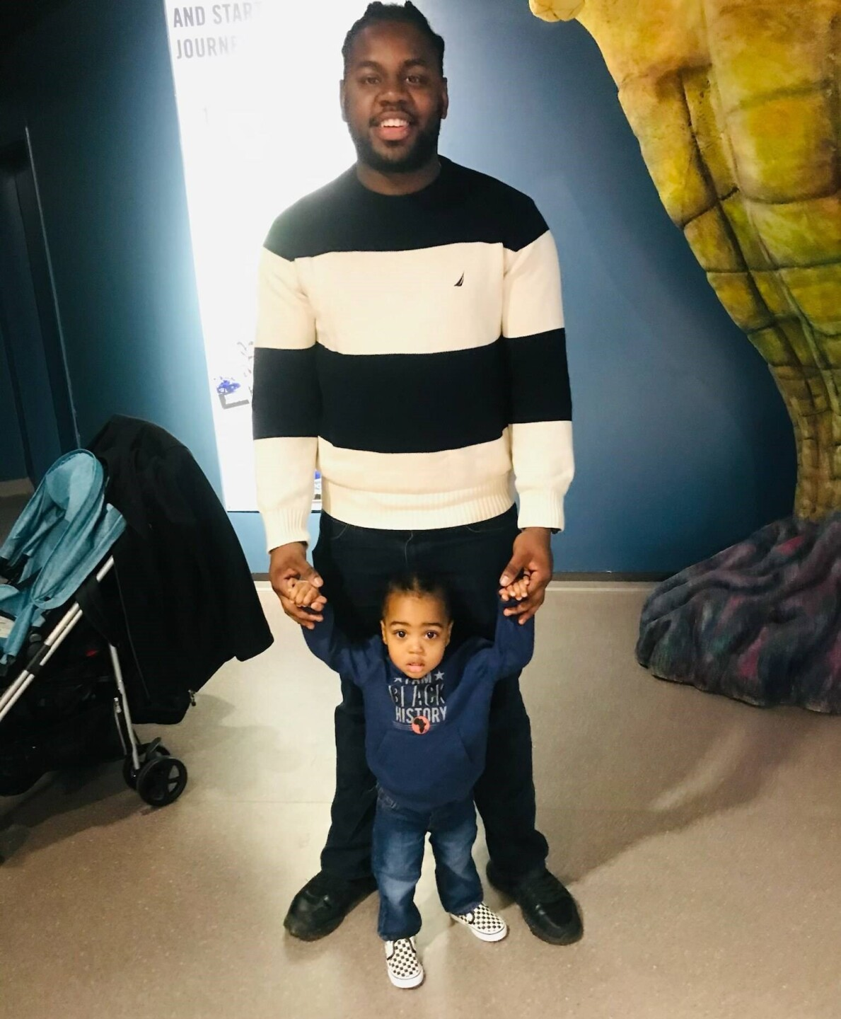 Rodney Walker is standing and holding his young son's hands in this photo.