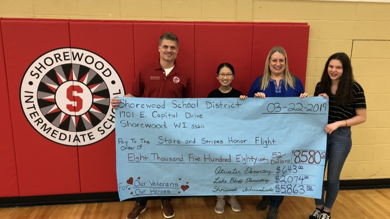 Shorewood schools students hold up poster of money raised for Stars and Stripes Honor Flight