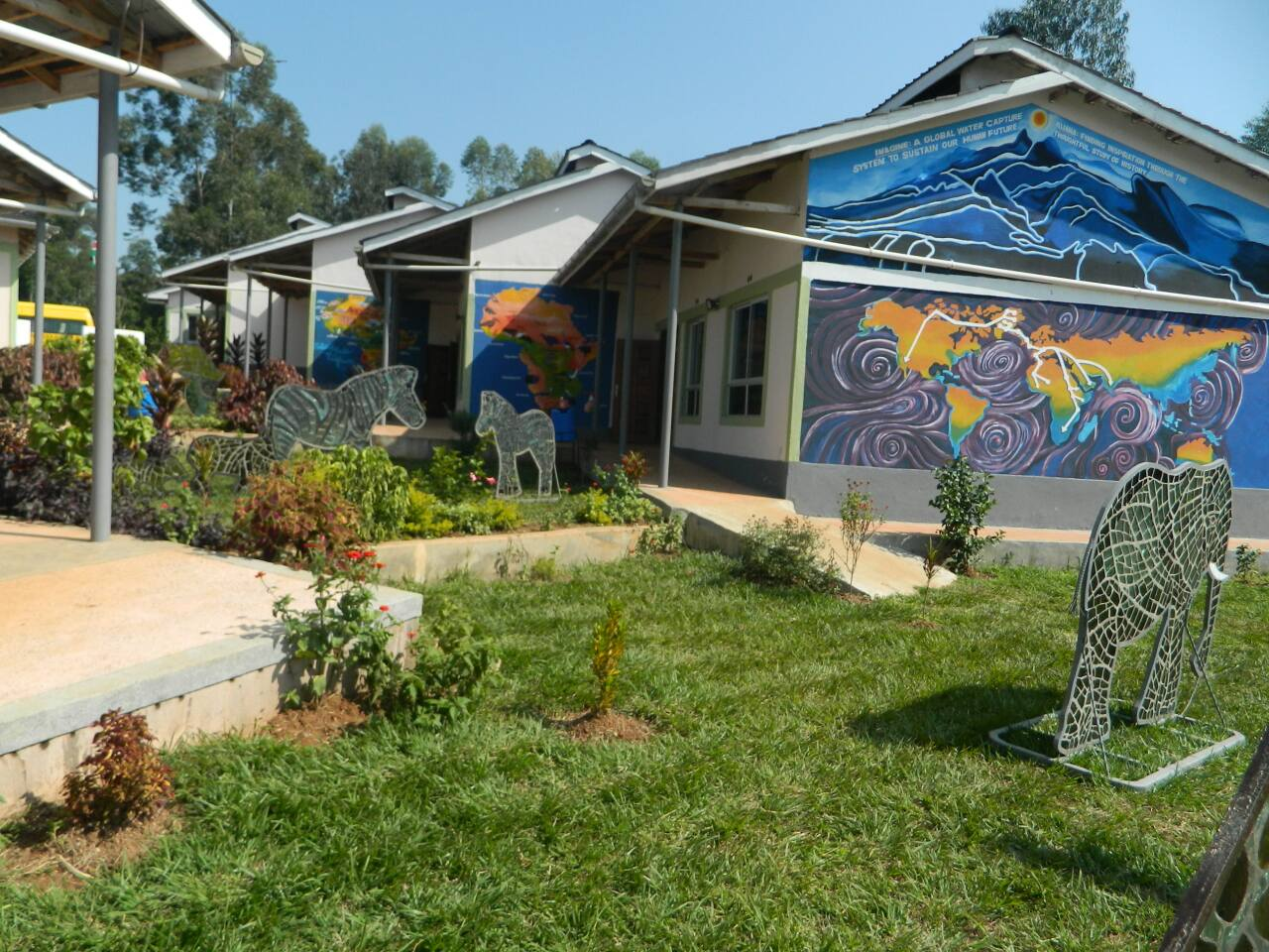 Murals of Africa painted on the sides of a school building.