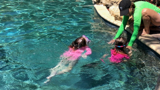 Kids swimming with mom watching