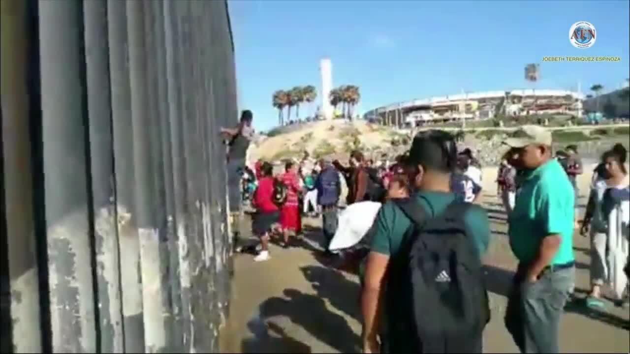 Migrants climb over border fence.jpeg