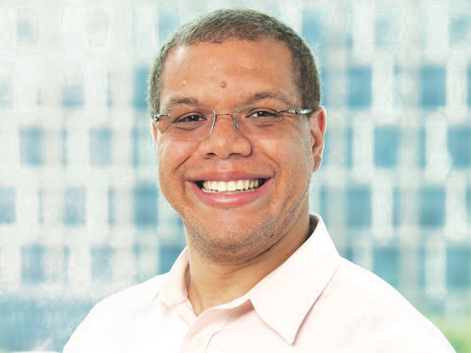 Michael Neal is smiling in this photo. He has short-cropped hair and is wearing glasses and a dress shirt.