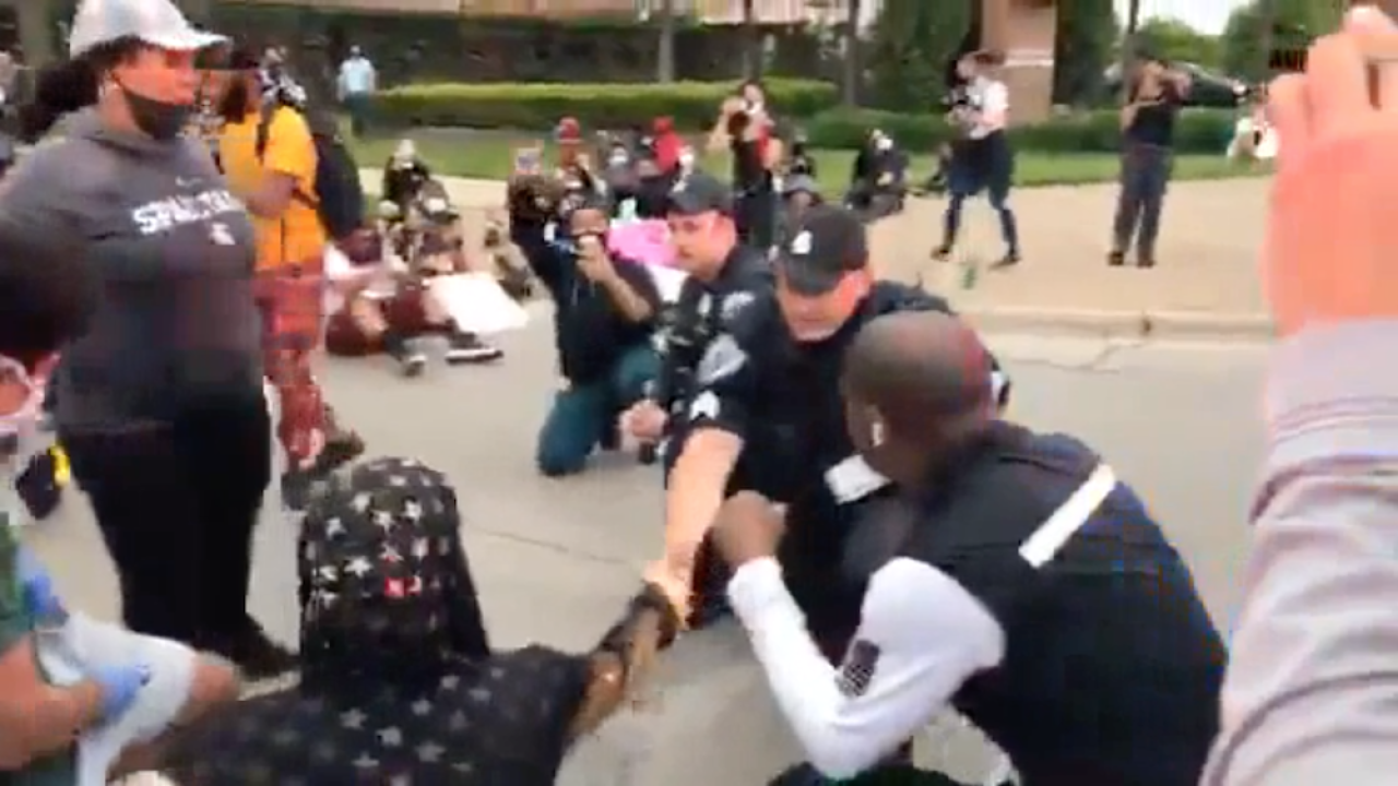 Police officers take a knee with protesters in Michigan