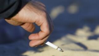 Hand holding lit cigarette