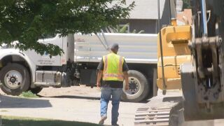 Crews with the Pueblo Board of Water works repair a water main break in 105 degree heat.