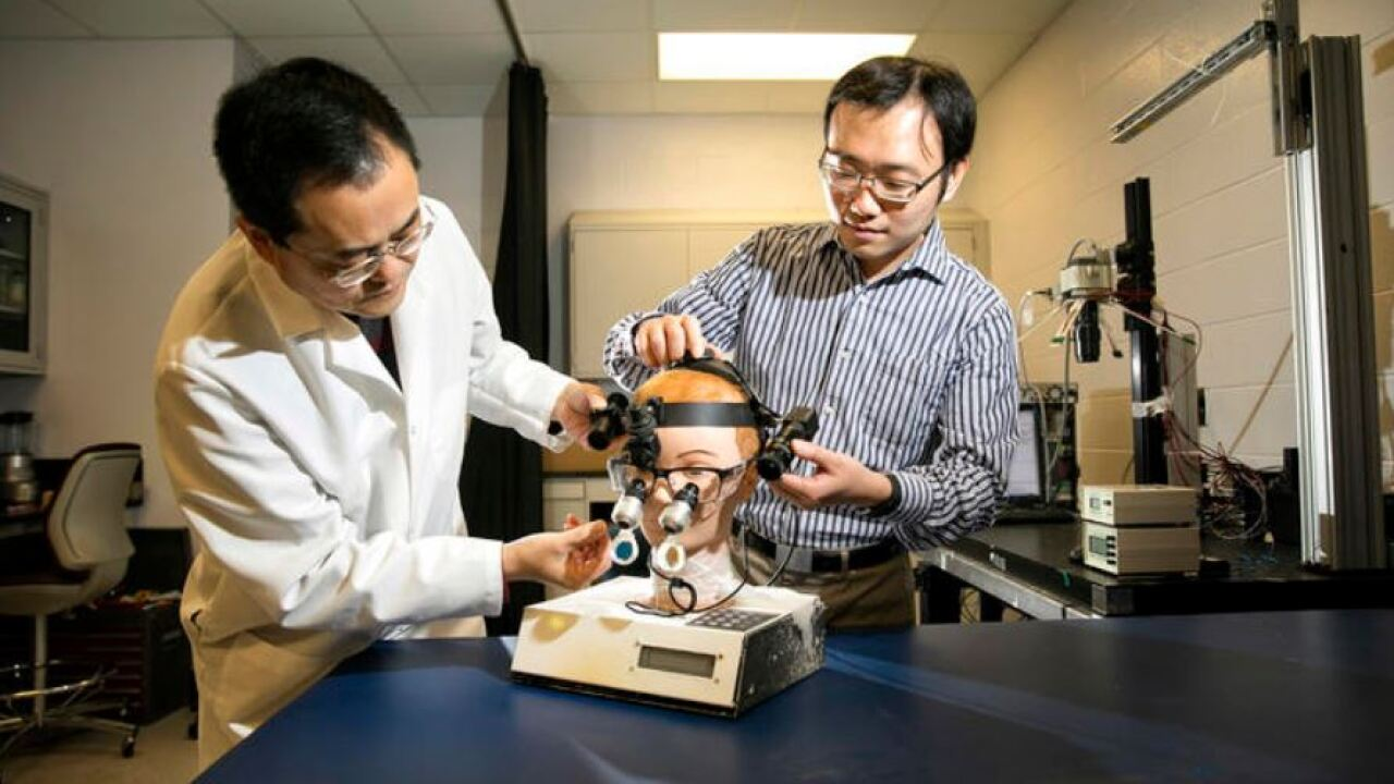 Guoqiang Yu (left) and Chong Huang are two of the four inventors who have developed glasses that can be worn during surgery to help neurosurgeons easily identify tumor margins during surgery. Mark Cornelison   UK Photo.