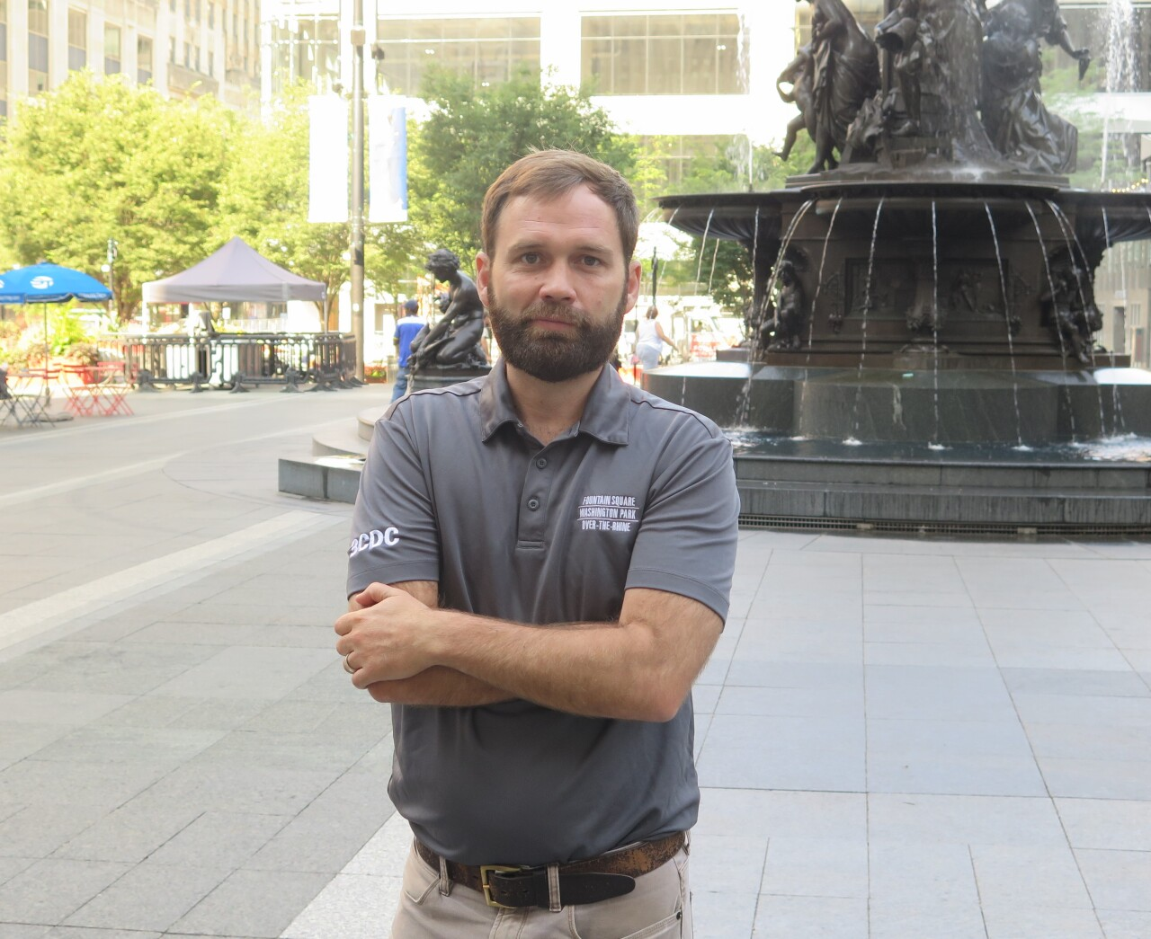 David Vissman poses for a photo at Fountain Square. He is wearing a grey shirt and has brown hair and a brown beard and mustache.