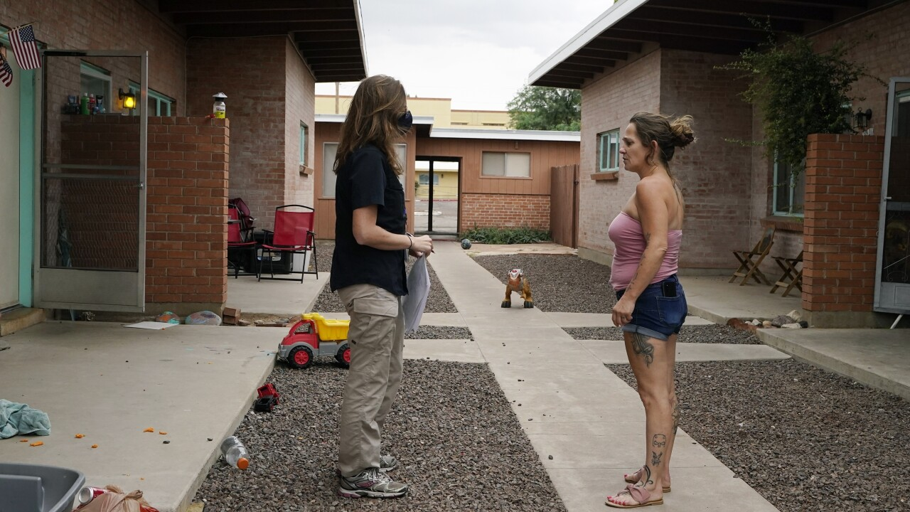 Pima County Constable Kristen Randall, left, speaks to a rental resident letting them know about their eviction notice Friday, Sept. 24, 2021, in Tucson, Ariz. Long delayed evictions are rolling out more than a month after the end of a federal moratorium that had protected tenants, including some who hadn't paid rent for many months during the coronavirus pandemic. (AP Photo/Ross D. Franklin)