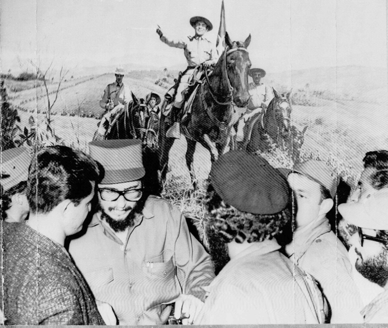 Fidel Castro is shown with a group of his soldiers in front of a mural showing ex-dictator Fulgencio Batista as an army Colonel leading troops through mountains of eastern Cuba. Castro viewed the mural at Batista's farm 15 miles southwest of Havana. This is a 1959 photo. (AP PHOTO)