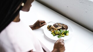 storyblocks-african-american-woman-eating-vegetables_S3etI4ghFw.jpg