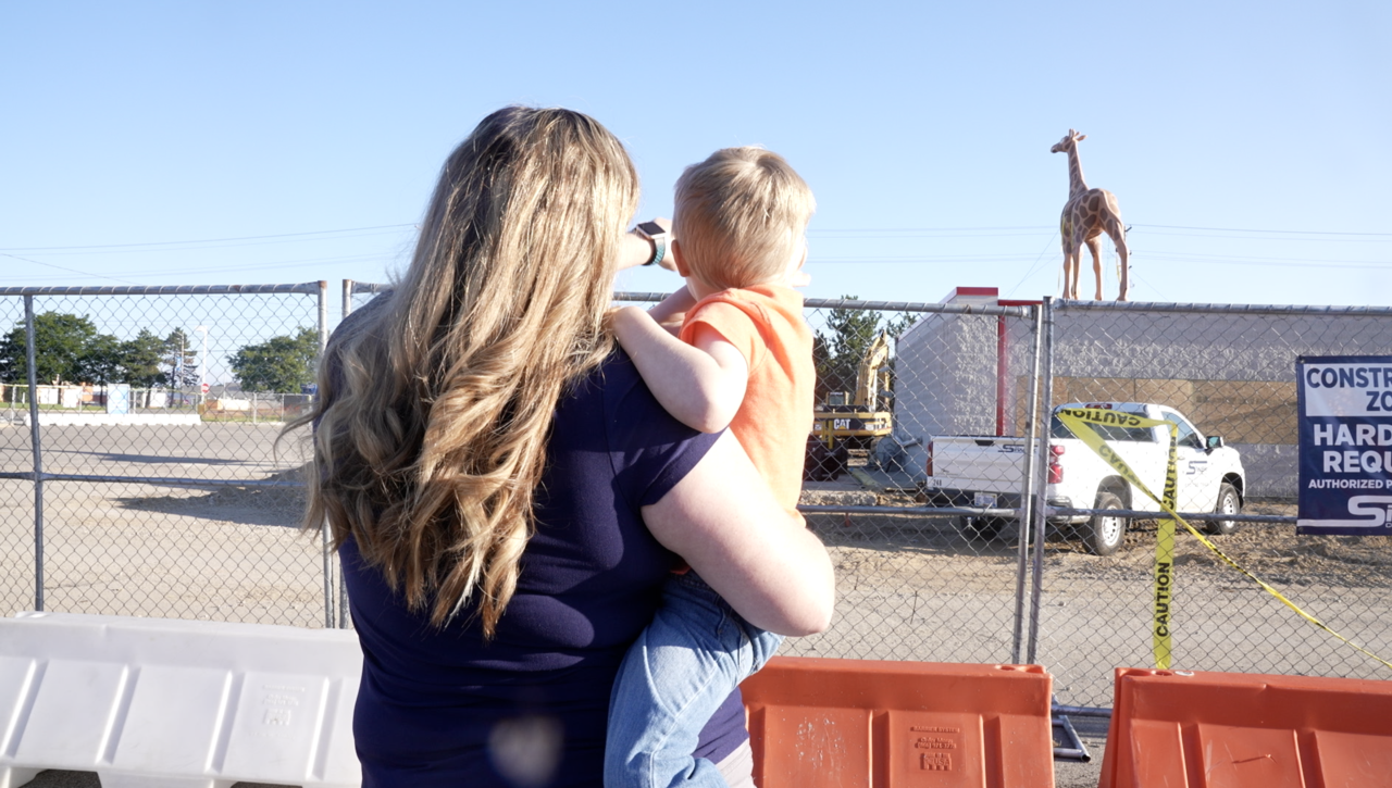 Titus Lassley and his mom DeAnn are looking at the giraffe.