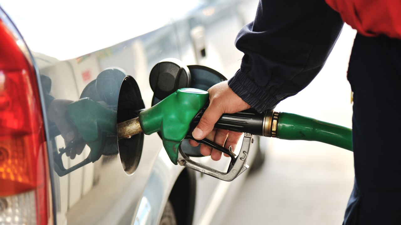 Close-up image of a mens hand refilling the car with a gas pump
