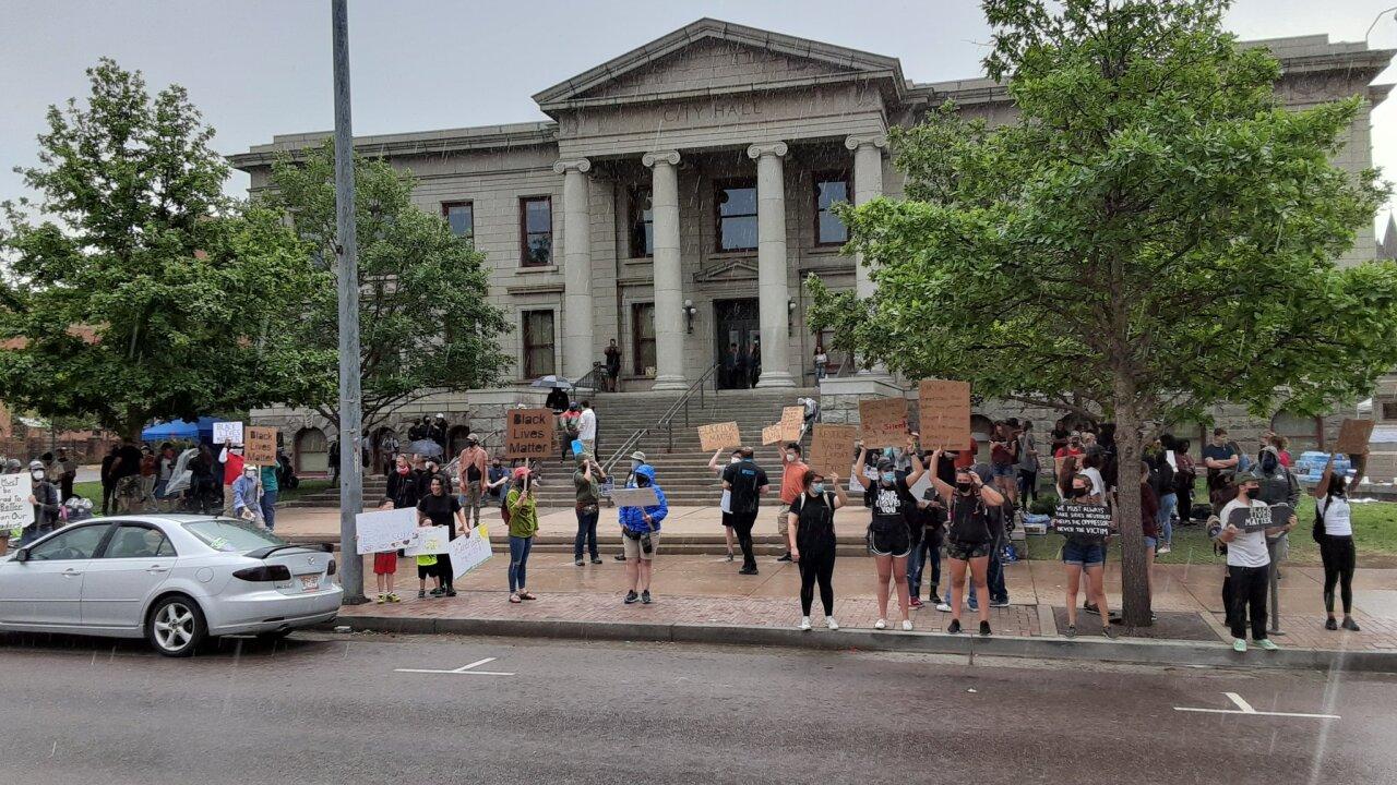 Protesters gather Saturday in Colorado Springs despite rainy conditions.