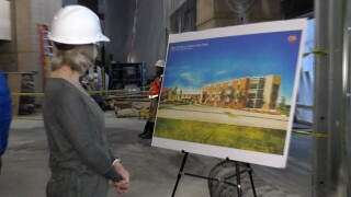 An attendee looks at a model of what the outside of the new main lobby and entrance will soon look like.