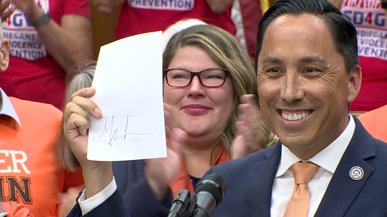 Todd Gloria holds up signed AB 893