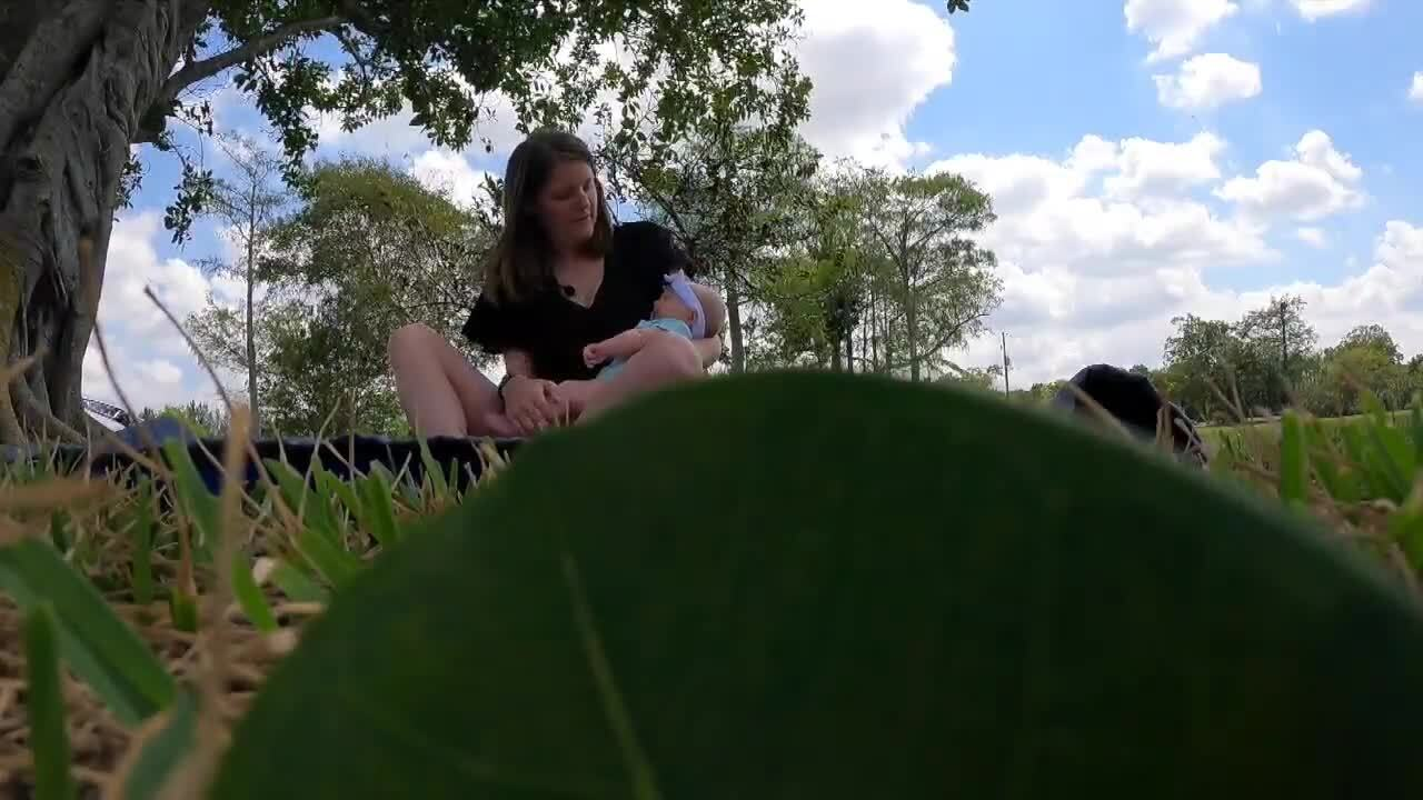 Mary-Kate, mother of baby girl born with COVID-19 antibodies, sits in grass while holding daughter Addison