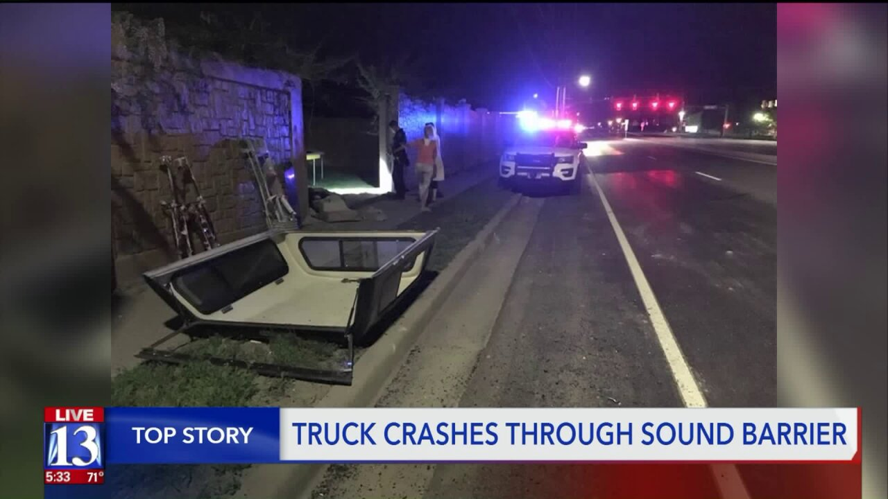Truck crashes through Kearns sound barrierwall