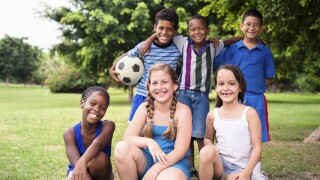 Multiethnic group of happy friends with soccer ball
