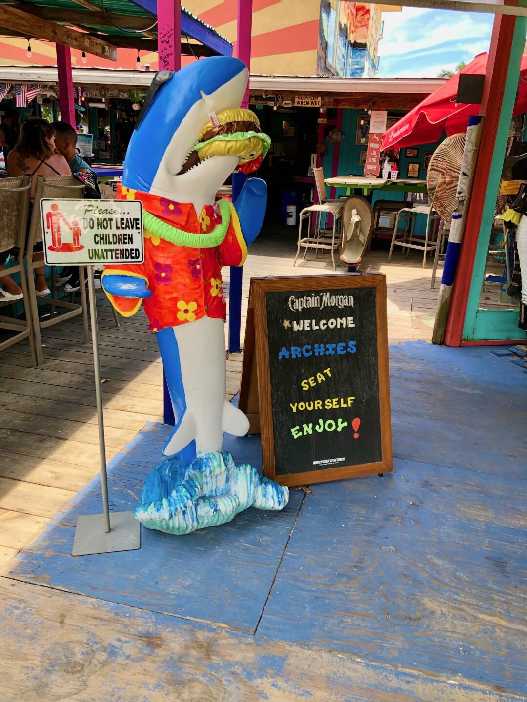 A shark eating a hamburger greats guest they enter.