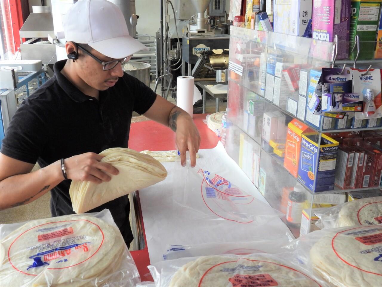 An employee packages freshly-made tortillas at San Antonio.jpg