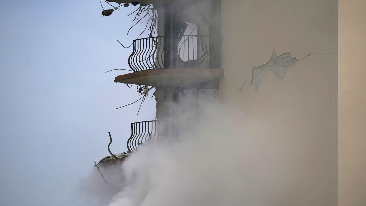 smoke rises from rubble of Champlain Towers South condo building, June 25, 2021