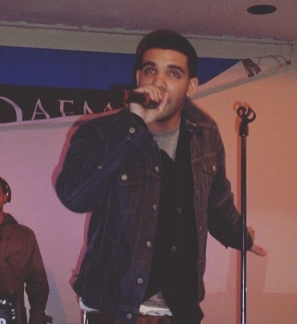 Photo of Drake performing at Daemen College with banner in the back.jpeg