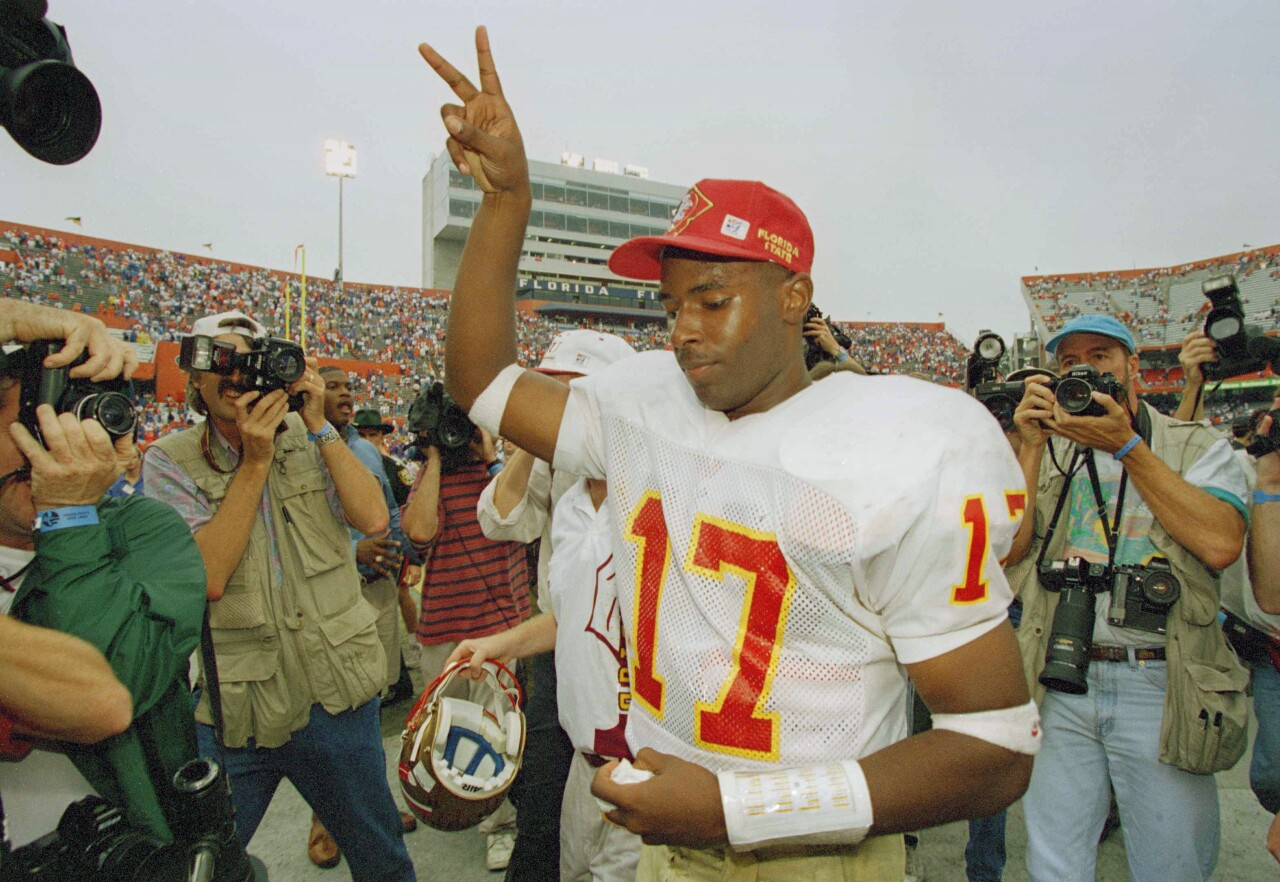 Florida State Seminoles QB Charlie Ward flashes victory sign while leaving field after beating Florida Gators in 1993