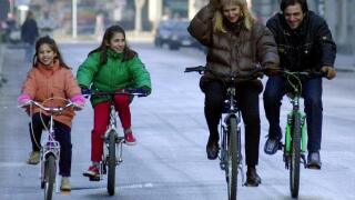 Family riding bicycles along street