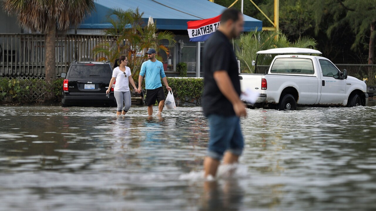 Yaneisy Duenas (L) and Ferando Sanudo walk through the flooded parking lot to their boat at the Haulover Marine Center on November 14, 2016 in North Miami, Florida. The flood waters are caused by the combination of the lunar orbit which causes seasonal high tides, also known as a King tide, and what some scientists believe is rising sea levels due to climate change.