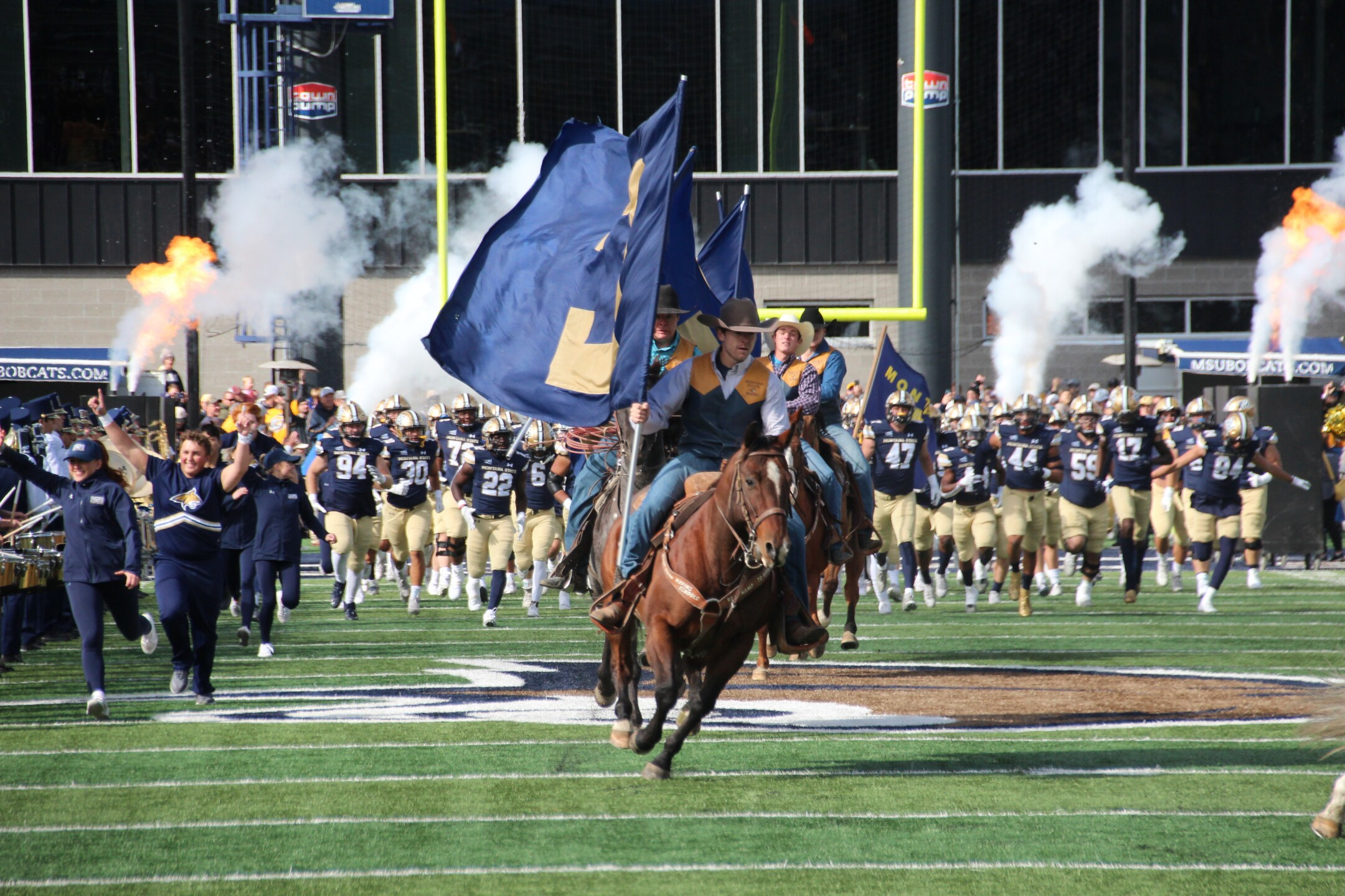 Montana State rodeo team rides in before the game