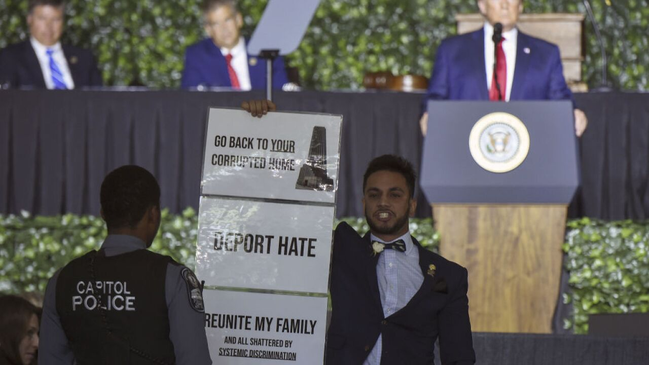 Virginia delegate disrupts President Trump's Jamestown speech with 'deport hate' sign