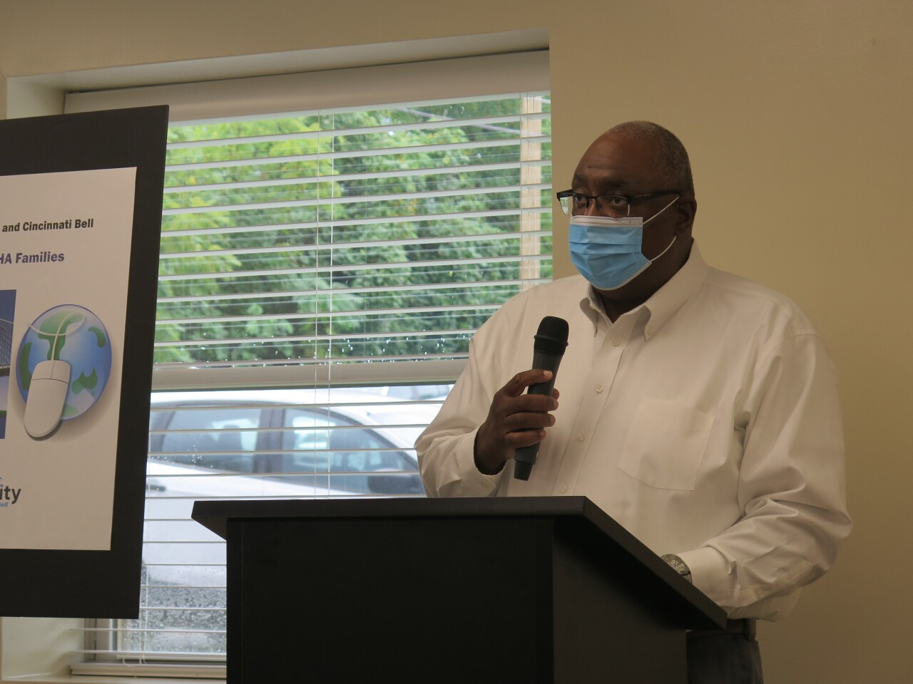Gregory Johnson speaking at a ribbon-cutting at Marianna Terrace on Aug. 30, 2021. He is holding a microphone and wearing a white dress shirt, glasses and a mask over his nose and mouth.