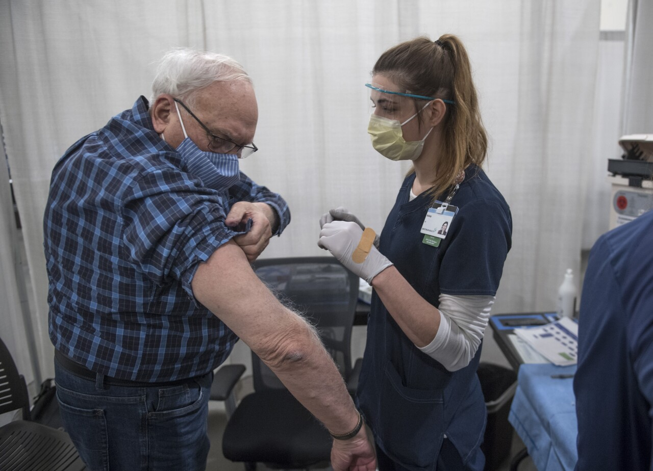 Man rolls up his sleeve to be vaccinated