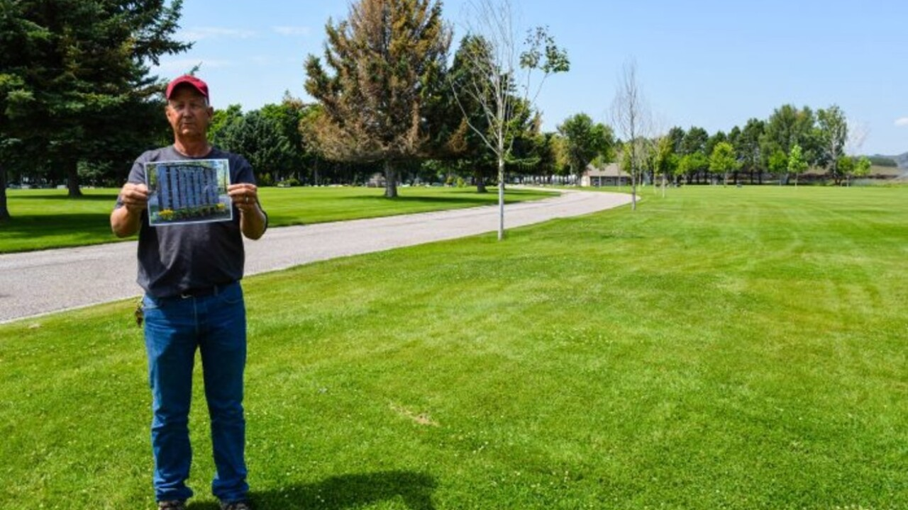 Missoula City Cemetery Director Ron Regan stands on the site of the proposed pet ossuary and memorial wall while showing a photo of a similar wall elsewhere. (Dave Stalling/Missoula Current)