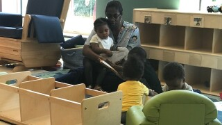 Teacher reading a book to students at daycare.