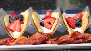 The finished pancake tacos topped with yogurt and berries, served with twisted strips of bacon.