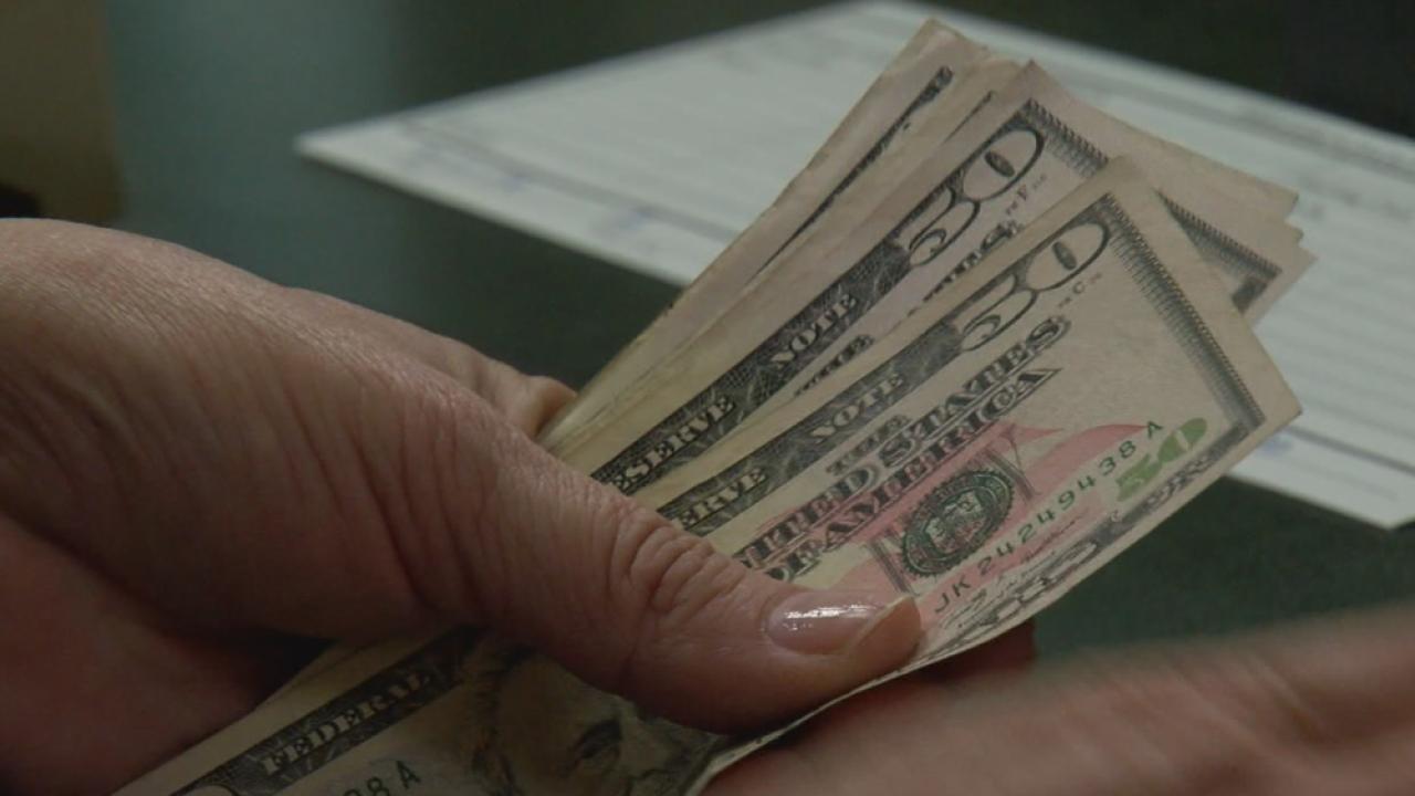 man holding $50 bills