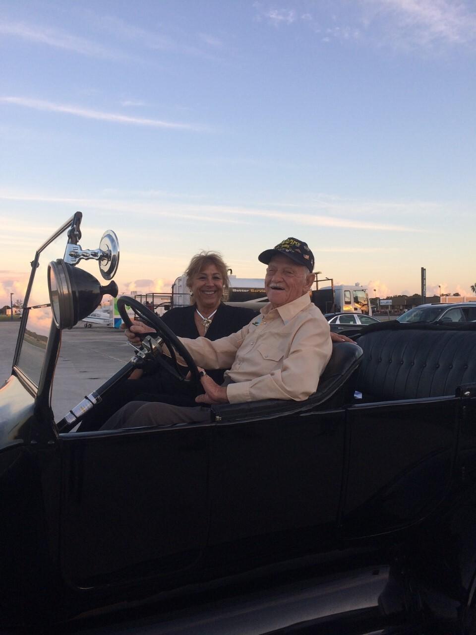 elderly man wearing white button up shirt riding a  black vintage convertible car.