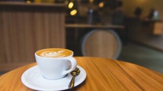 latte in white cup on white plate in empty coffee shop